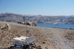 Monitoring equipment on the active volcano, Nea Kameni, with a view of a cruise ship and Fira in the background