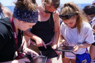 Laura, Leah, and Emily figuring out how to use a GIS application on the iPads