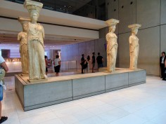 Figure 3: According to Greek preservation laws, any and all cultural assets are to be protected and preserved by the Greek State. To further protect more valuable parts of the Acropolis, some artifacts and sculptures have been moved to the Acropolis Museum. This includes the Caryatids, with their place of origin, the Erectheion, now housing replicas that have been reinforced with metal rods and pillars of new marble. (2)