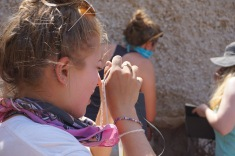 Emily using her hand lense to identify minerals in pumice