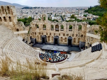 That was a close one! Well, here we are at our next stop: The Odeon of Herodes Atticus on the southwest of the Acropolis! Built in 161 AD, this stone amphitheater can fit up to 5000 people! Music concerts were held here until 267 AD, when the Heruli destroyed it. (1)